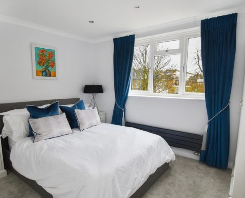 Blue pinch pleat curtains in bedroom