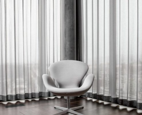 A commercial wave curtain in a sheer fabric fitted on a Silent Gliss 3840 track