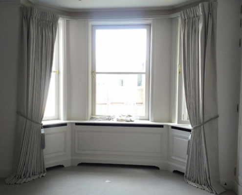 Bay track with pinch pleat curtains in a grey fabric
