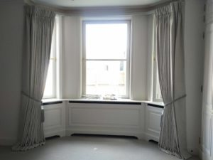 Bay window curtain track with pinch pleat curtains in a grey fabric
