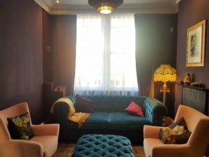 Exquisite bespoke ottoman in a green velvet with purple floor to ceiling curtains