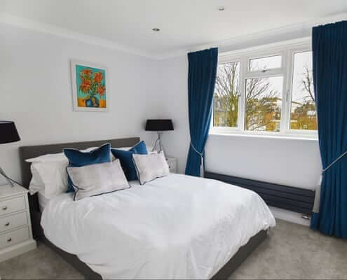 Made to measure curtains London, a lovely teal fabric fitted on a pole in a modern bedroom