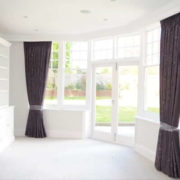 Pinch pleat curtains London on a bay window, fitted on a ceiling fitted custom metal track in a dark fabric