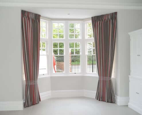 Pinch pleat curtains London on a bay window on a ceiling fitted track in North London