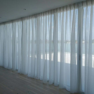 Contract curtains made of wave voile for a large window made ceiling to floor on a curtain track