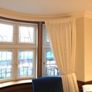 White cotton curtains for bay windows on a custom track in London