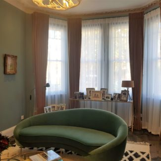 Beautiful bay window curtains in London Fitzrovia in a mustard fabric fitted on a bespoke pelmet