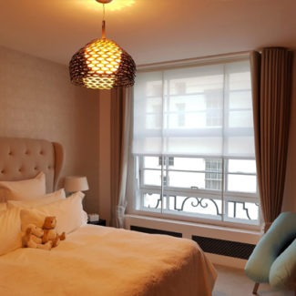Curtains London in London Mayfair. Wave curtains and roller blind behind in a lovely modern bedroom