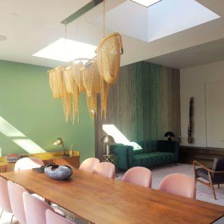 Lovely interiors, handmade green velvet sofa with floor to ceiling velvet curtains in London Fulham