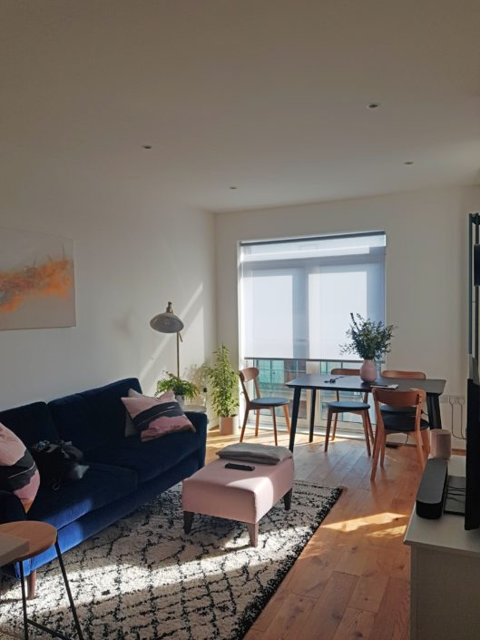A colourful and bright living room with a grey filter blind